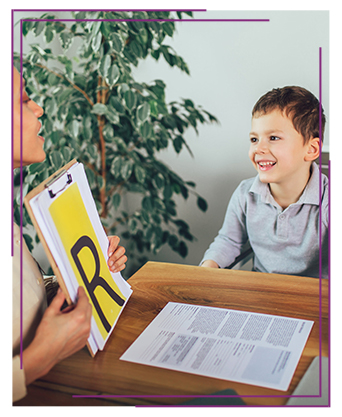 Young boy working with his teacher and letters