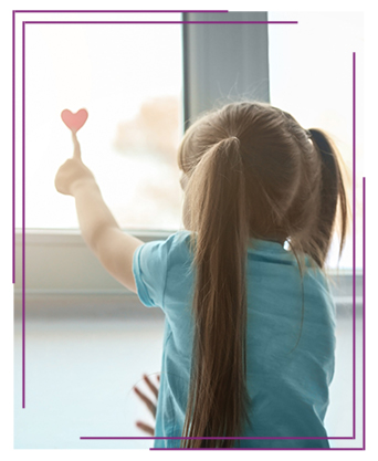 Little girl looking out the window with a heart