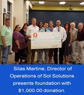 Silas Martine, Director of Operations of Sol Solutions presents foundation with $1,000.00 donation