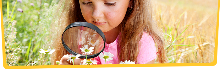 Girl studying flowers through magnifying glass