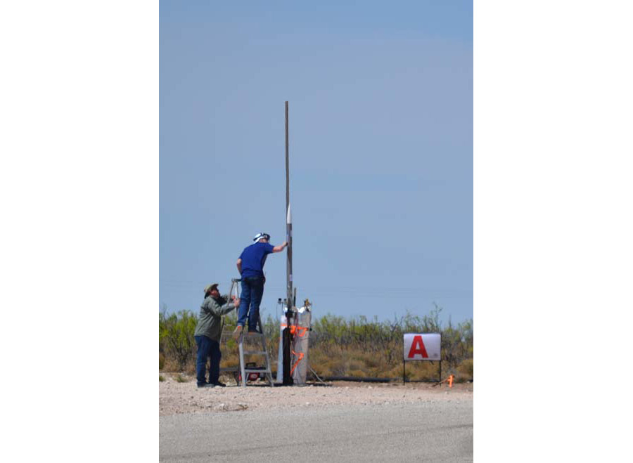 Two men setting up rocket for launch