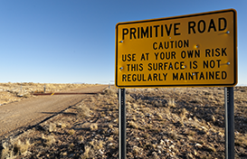 Primitive Road sign cautioning drivers to use at their own risk