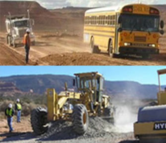 Heavy road equipment and school bus on dirt road