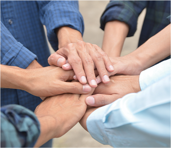 group of adults joining hands