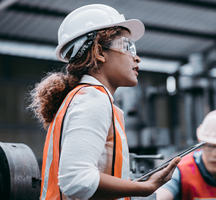 Woman in hard hat surveying building
