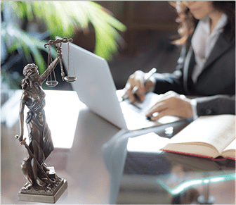Lady sitting at a desk with a mini justice paper holder