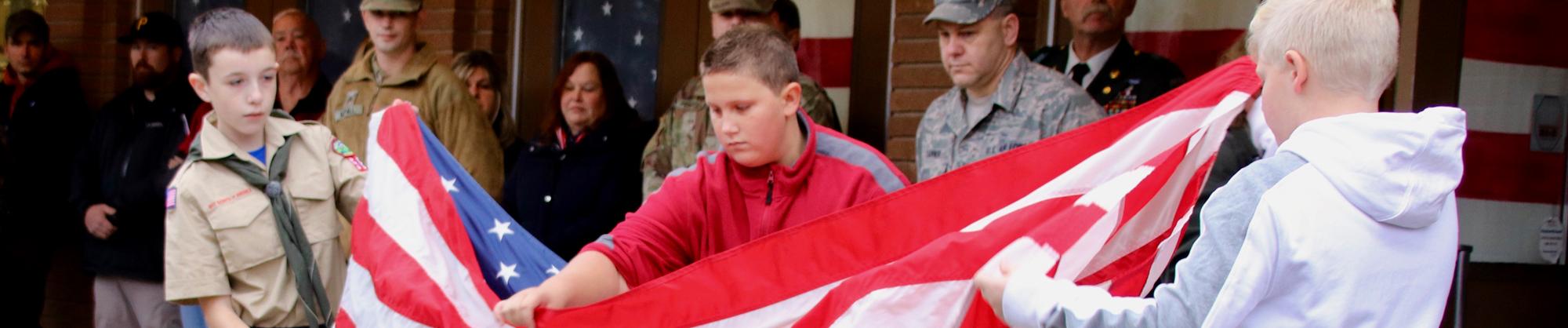 three boys folding the United States of America Flag