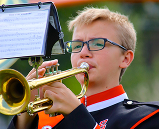 male student playing his trumpet