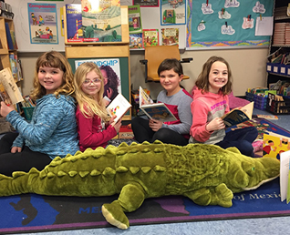 four student reading books on a stuffed alligator