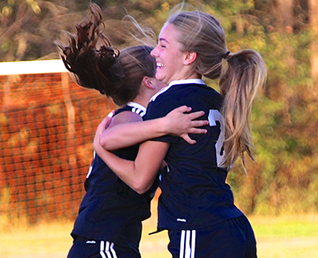 two female soccer players hugging