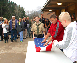 three boys folding the United States flag