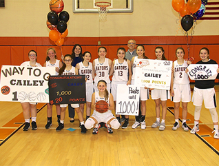girls basketball team holding signs