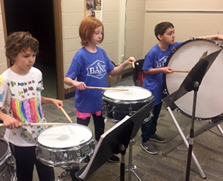 three students playing the drums