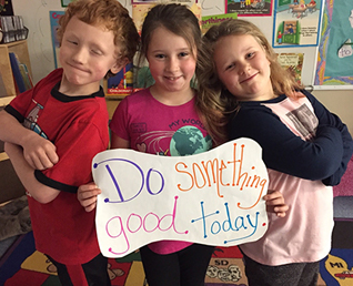 three students holding a sign that says Do something Good Today.