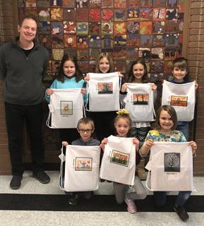 Students holding artwork