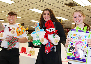 three students with stuffed animals and gifts