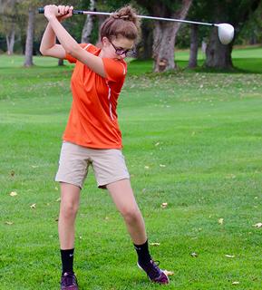female playing golf
