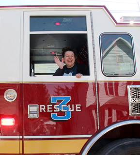 staff member riding in a firetruck