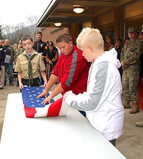 three boys folding the USA flag