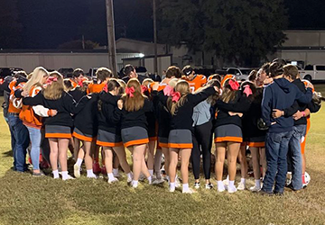 Football team and cheerleaders huddling together on a field