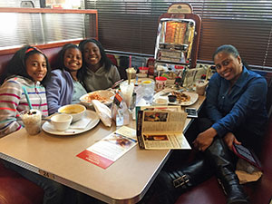 Happy students with an adult sitting a diner table