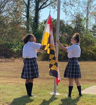 Two happy middle school girls raising the school flag