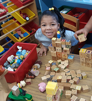 Cute young school girl smiling up from table with blocks