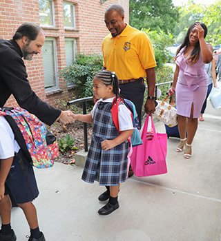 Families greeted by Rev. Baer coming to school