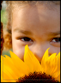 Female student hiding behind a sunflower