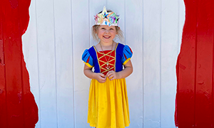 Smiling female student dressed as Snow White and wearing a colorful paper crown