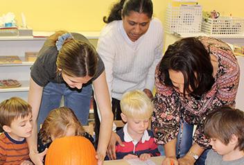 teachers with children and pumpkin