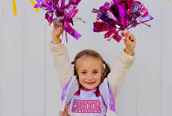 little girl cheering with pom poms