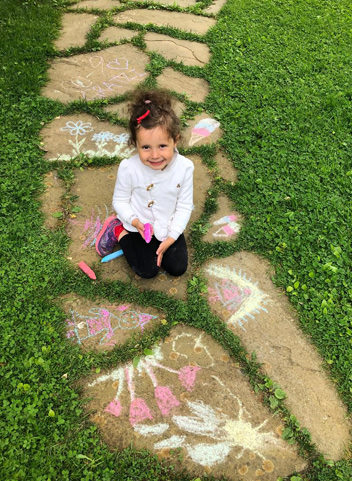 a student with her sidewalk chalk art
