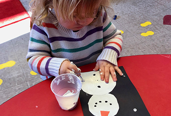 little girl painting a snowman