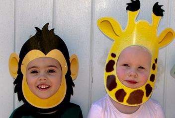 two children, one with a monkey mask and another with a giraffe mask