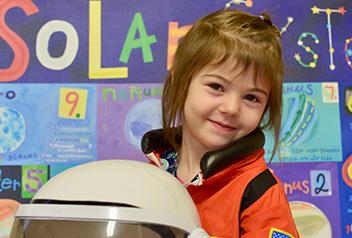 girl in astronaut suit holding a helmet