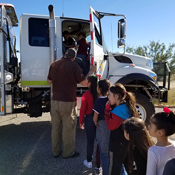 students in line waiting to look at a semi-truck