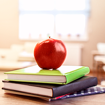a red apple sitting on a stack of books