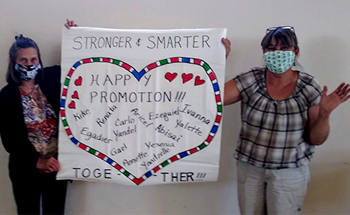 two teachers holding a sign with a heart on it