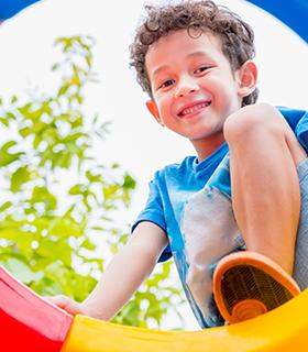 Elementary school boy outside on playground equipment