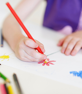 Elementary student coloring with pencils