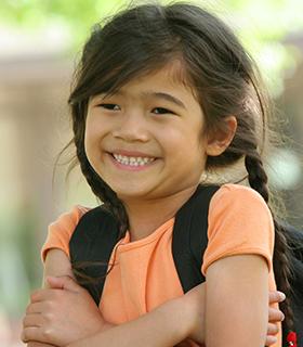 Happy school girl with backpack