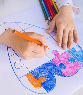 Student coloring in a heart on paper