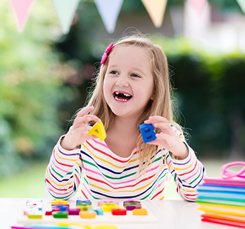 Smiling girl with letter toys