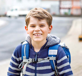 boy with blue jacket and backpack outside