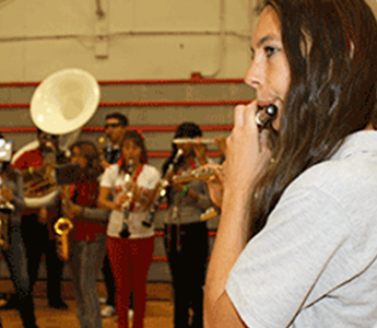 Student playing an instrument in the gym