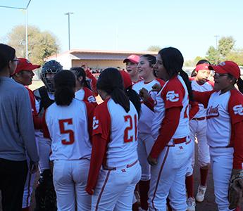 Girls baseball team in a huddle