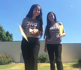 Two happy students wearing JAG t-shirts