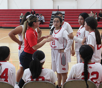 Coach talking with girls basketball team during game