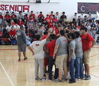Students huddling up on the basketball court during spirit week